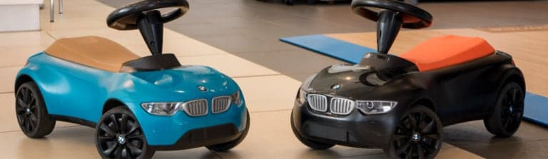 Two BMW baby racers sitting in a showroom.